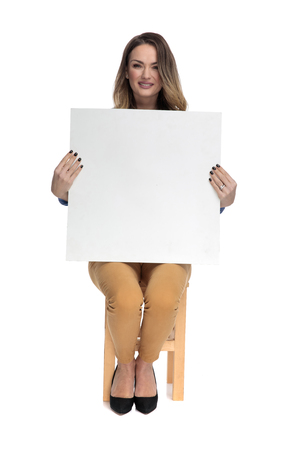 businesswoman sitting  holds a white bilboard and smiles while looking at the camera on a light background, full body picture