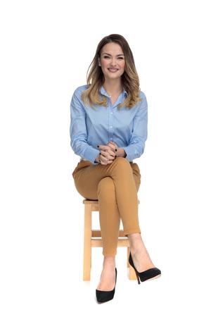 Joven mujer vestida casual sentada en una silla de madera con las piernas cruzadas y esperando la entrevista, foto de cuerpo completo