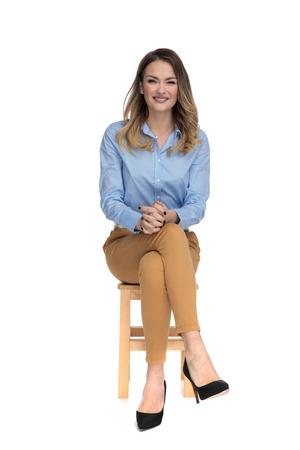 young casual dressed woman sitting on wooden chair with legs crossed and waiting for interview, full body picture