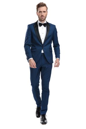 serious man in blue tuxedo walking on white background