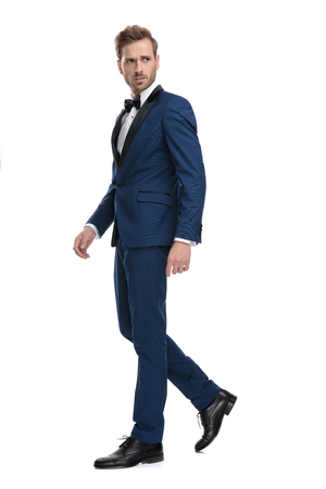 side view of worried man in blue tuxedo walking while looking away on white background