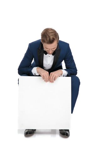 seated blonde haired man in blue tuxedo looking down to an empty paper billboard on white background Banco de Imagens