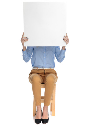 smart casual woman sitting on stool holds advertisement on white background Stock Photo