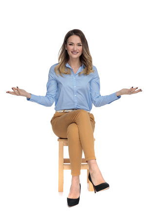 young beutiful woman sits on wooden chair on white background and makes inviting gesture