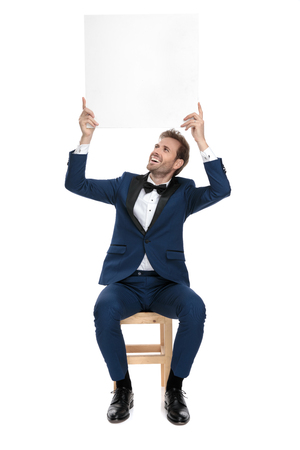 seated happy man in blue suit holding a blank billboard up in the air on white background Stock Photo