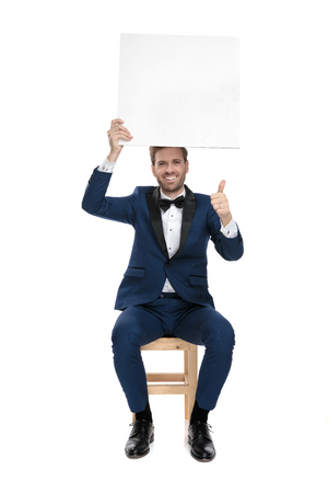 seated handsome man in blue tuxedo showing ok gesture while holding an empty billboard up in the air on white background