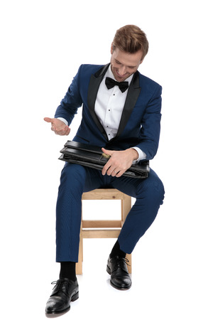 seated sexy man in blue suit looks at briefcase he holds on his lap on white background