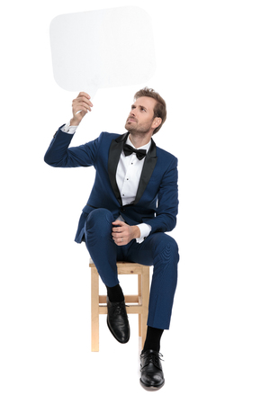 seated astonished man in blue costume holds a blank chat bubble up in the air on white background