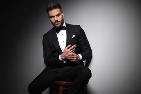 sitzender Mann im schwarzen Smoking, der die Hände auf grauem Hintergrund zusammenhält Standard-Bild