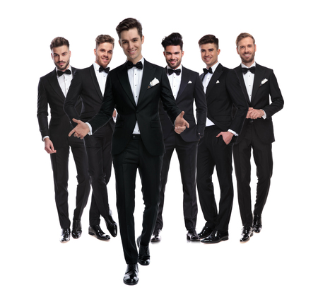 smiling young man in tuxedo walks in front of his elegant team of men and welcomes on white backgrouond