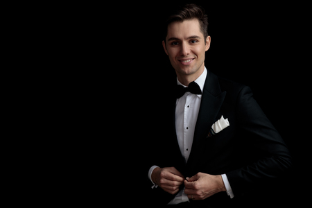 fashion happy man in black tuxedo buttoning his lounge jacket on black background