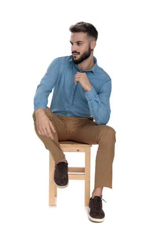 relaxed man in blue jeans shirt sitting with elbow on leg while looking away on white background Stock Photo