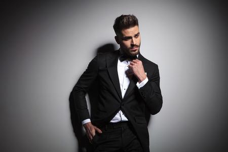 caucasian guy in black tuxedo adjusting bowtie on gray background Imagens