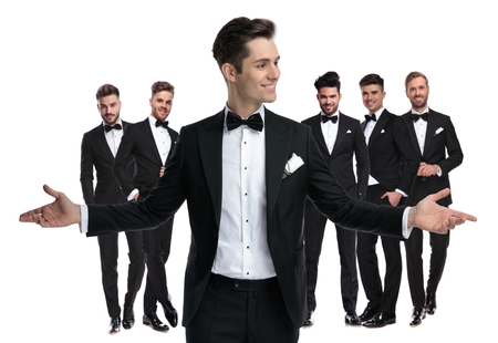 happy young groom welcomes you to be his best man , standing in front of his elegant team of men on white background