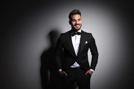 happy guy in black tuxedo standing with hands in pockets on dramatic studio background Stock Photo