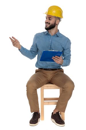 ingénieur attrayant avec casque de sécurité jaune assis et saluant avec un presse-papiers à la main sur fond blanc Banque d'images