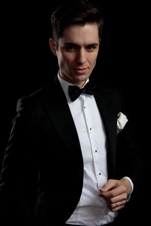 Novio atractivo en esmoquin negro despertando con su mirada sobre fondo negro