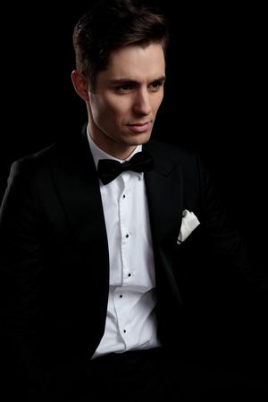 Hombre de negocios serio en esmoquin negro mirando a otro lado sobre fondo negro