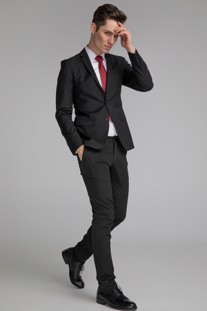 handsome man in black suit stepping and thinking with hand in pocket and at forehead on grey background