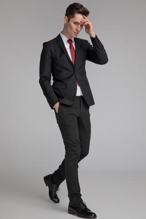 Hombre guapo en traje negro caminando y pensando con la mano en el bolsillo y en la frente sobre fondo gris