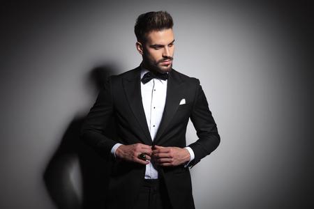 fashion guy in black tuxedo unbuttoning his suit on gray studio background