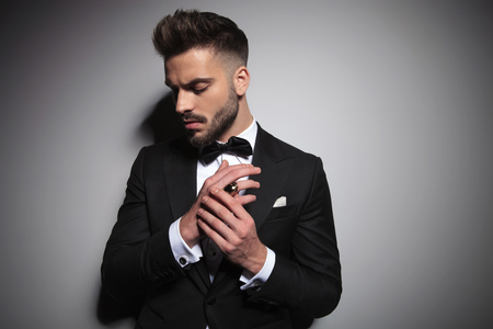 ernster Kerl im schwarzen Smoking, der die Hände zusammen auf grauem Studiohintergrund hält Standard-Bild