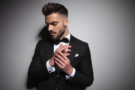 serious guy in black tuxedo holding hands together on grey studio background Banco de Imagens