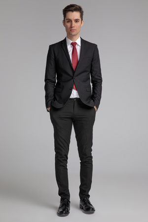 man in black suit standing with hands in pockets and looking forward on grey background