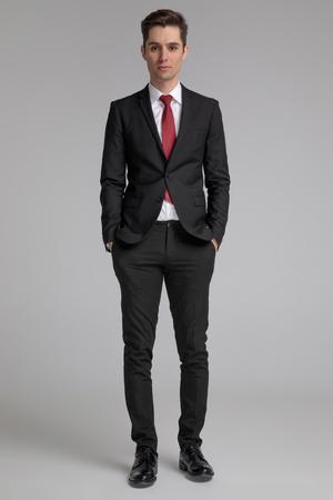 Mann im schwarzen Anzug, der mit den Händen in den Taschen steht und sich auf grauem Hintergrund freut