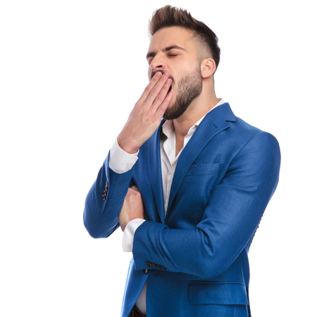 tired man in suit yawning with hand at mouth on white background Stockfoto