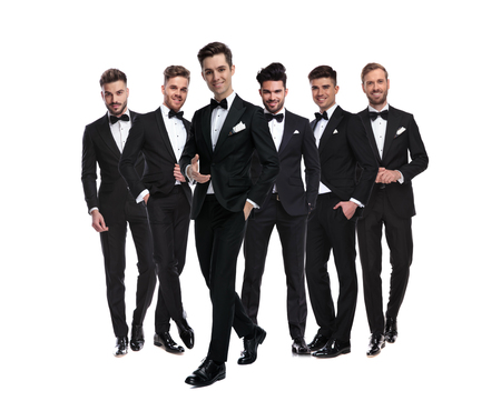 happy young man in tuxedo and bowtie pointing hand while walking in front of his team of elegant men on white background