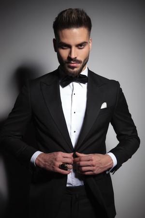 model guy in black tuxedo unbuttoning his suit on dramatic studio background