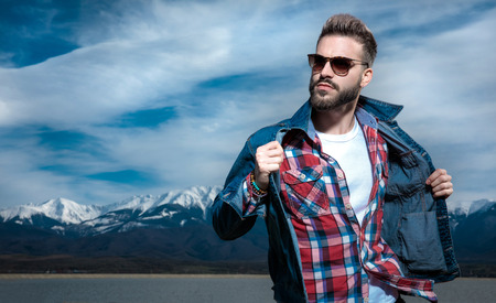 cool young guy in sunglasses pulls his jacket's collar and looks away to side , againse blue sky and mountains in the background Stock fotó