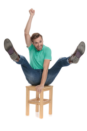 seated modern man in green polo shirt acting like a cowboy riding a chair with hand up in the air on white background