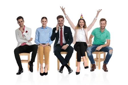 Super emocionado empresario celebrando con las manos en el aire mientras espera sentado en una silla con otras personas felices sobre fondo blanco.