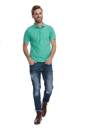 jonge man in een groen poloshirt die met de handen in de zakken loopt terwijl hij wegkijkt op een witte achtergrond Stockfoto
