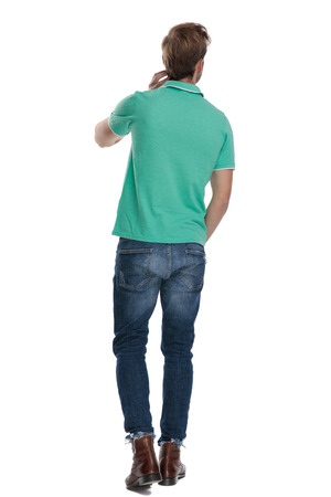 back view of a man in green polo shirt standing with hand at head on white backgroung