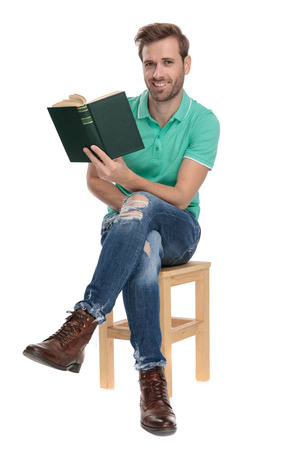 seated happy man in green polo shirt holding a book in hand with legs crossed on white background 版權商用圖片