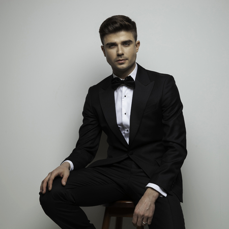 attractive man in tuxedo standing on wood chair on gray background