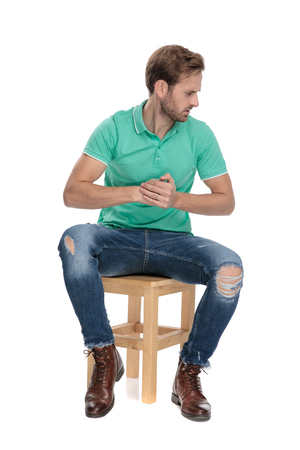 seated displeased man in green polo shirt threatening with his fists while looking away on white background