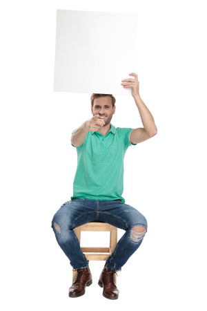 seated cool man in green polo shirt pointing finger to camera while holding an empty paper advertisement board up in the air on white background