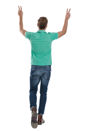 young man in green polo shirt walking back with hands up showing V sign on white background Stock Photo