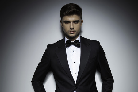 business young attractive guy in tuxedo standing on dramatic background