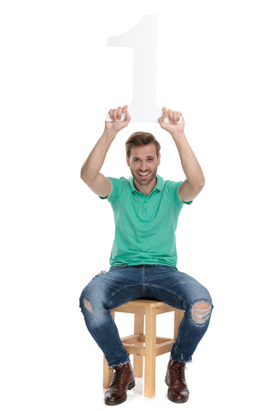 modern guy in green polo shirt holds number one sign up in the air while sitting on chair on white background