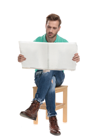 seated guy in green polo shirt with crossed legs reading newspaper on white background