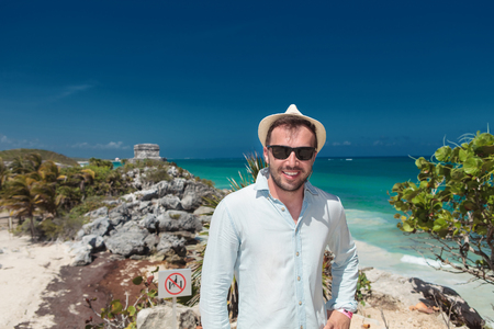 smiling young tourist visiting the ruins of Tulum, in Mexico, near the beach against blue sky Фото со стока
