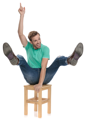 attractive man in green polo shirt riding a chair like at rodeo being a cowboy on white background