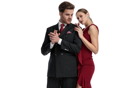 Confident man looking to the side, rubbing his hand and wearing a black suit while his girlfriend wearing a red dress is leaning on him, standing on white studio background Stockfoto