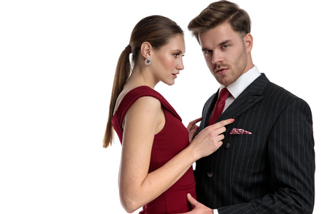 Amorous couple holding each other while the man dressed with a black suit is looking to the camera and the girl wearing a red dress romatically stares at him , on white studio background Stockfoto