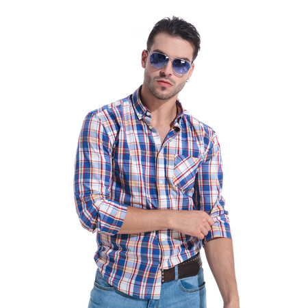 Confident man looking to the camera and adjusting his sleeve while wearing a checkered shirt and pair of sunglasses, standing on white studio background